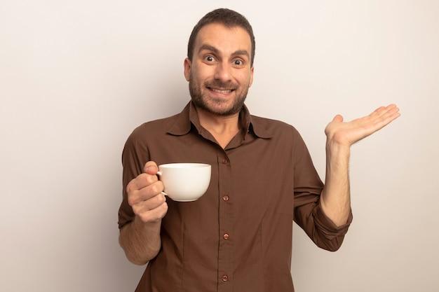복사 공간 흰색 배경에 고립 된 빈 손을 보여주는 카메라를보고 차 한잔 들고 웃는 젊은 백인 남자