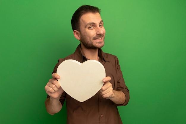 Sorridente giovane uomo caucasico tenendo la forma di cuore guardando la telecamera isolata su sfondo verde con copia spazio