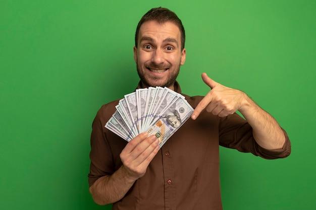 복사 공간 녹색 배경에 고립 아래쪽을 가리키는 카메라를보고 돈을 들고 웃는 젊은 백인 남자