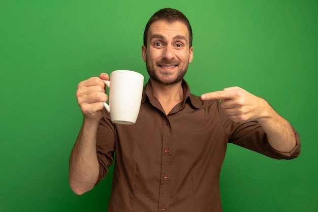 Smiling young caucasian man holding and pointing at cup of tea looking at camera isolated on green background