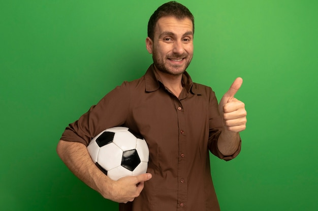 Sorridente giovane uomo caucasico tenendo il pallone da calcio guardando la telecamera che mostra il pollice in alto isolato su sfondo verde con copia spazio