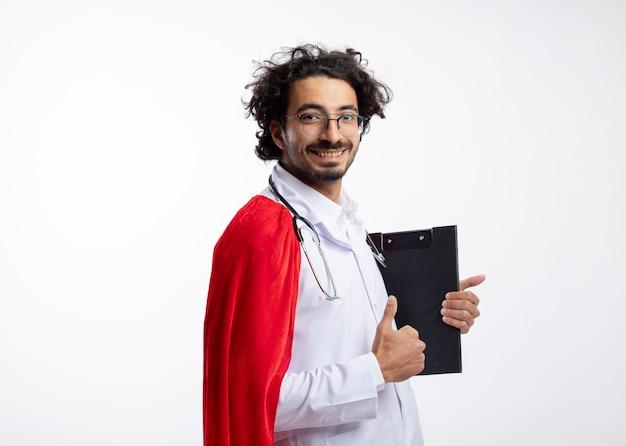 赤いマントと聴診器を首にかけた医者の制服を着た光学ガラスの若い白人男性の笑顔は、クリップボードと親指を上に持って横に立っています