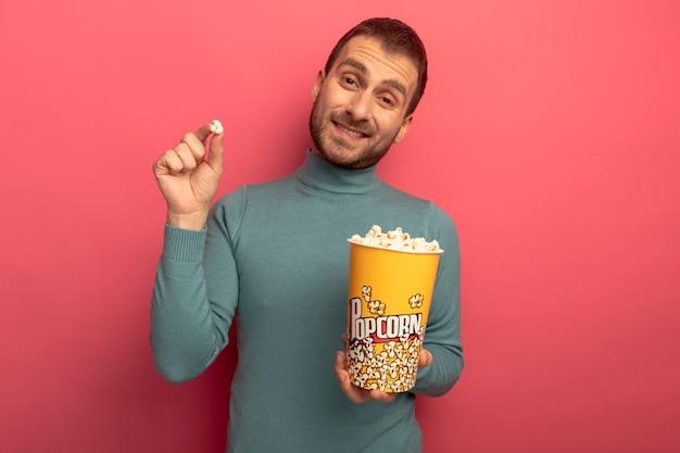 Улыбающийся молодой кавказский мужчина смотрит в камеру, держа ведро попкорна и кусок попкорна, изолированные на малиновом фоне с копией пространства