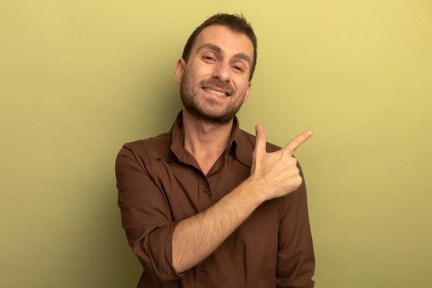 복사 공간 올리브 녹색 배경에 고립 된 측면에서 가리키는 카메라를보고 웃는 젊은 백인 남자