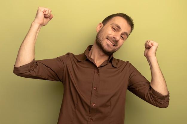 올리브 녹색 배경에 고립 뒤에 가리키는 카메라를보고 웃는 젊은 백인 남자