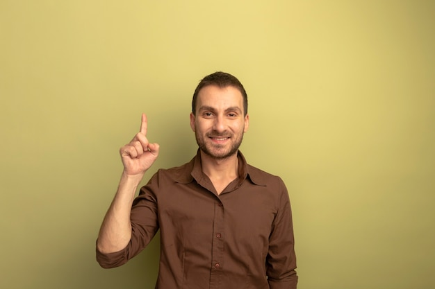Smiling young caucasian man looking at camera pointing up isolated on olive green background with copy space