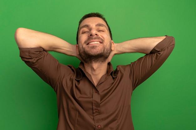 Sorridente giovane uomo caucasico guardando la telecamera mettendo le mani dietro la testa isolata su sfondo verde