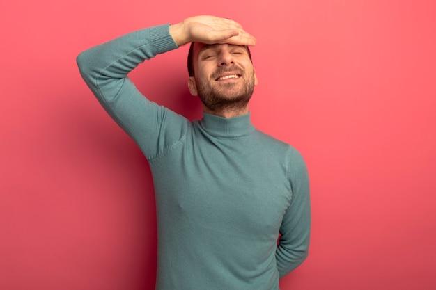 コピースペースのある深紅色の壁に隔離された背中の後ろに別の手を保ちながら目を閉じて額に手を置いて笑顔の若い白人男性