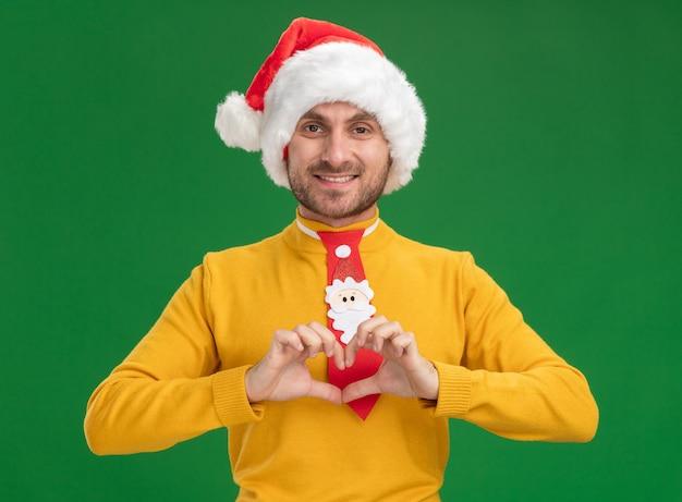 Улыбающийся молодой кавказский мужчина в рождественской шляпе и галстуке делает знак сердца, глядя в камеру, изолированную на зеленом фоне