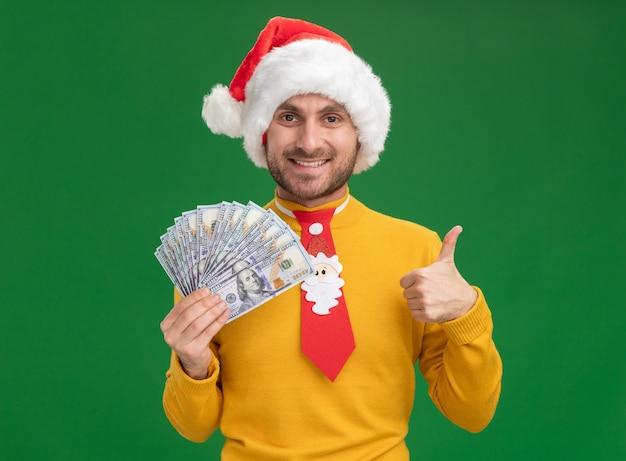 クリスマスの帽子とネクタイを身に着けている若い白人男性の笑顔は、緑の背景に分離された親指を示すカメラを見てお金を保持しています