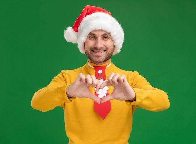 Улыбающийся молодой кавказский человек в рождественской шляпе и галстуке, смотрящий в камеру, делает знак сердца на зеленом фоне
