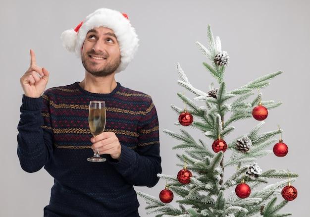 Sorridente giovane uomo caucasico che indossa il cappello di natale in piedi vicino all'albero di natale tenendo il bicchiere di champagne guardando e rivolto verso l'alto isolato su sfondo bianco