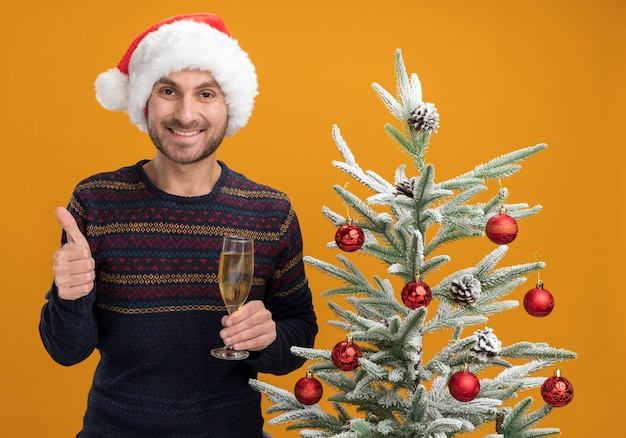 Smiling young caucasian man wearing christmas hat standing near decorated christmas tree holding glass of champagne looking  showing thumb up isolated on orange wall
