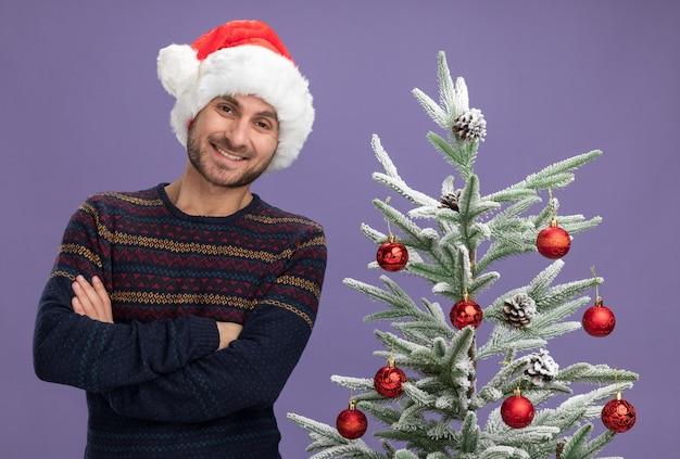 보라색 벽에 고립 된 찾고 장식 된 크리스마스 트리 근처 닫힌 자세와 크리스마스 모자 서 입고 웃는 젊은 백인 남자
