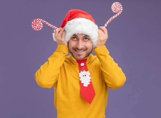 Smiling young caucasian man wearing christmas hat and tie holding christmas sweet canes looking up making reindeer antlers with canes isolated on purple background