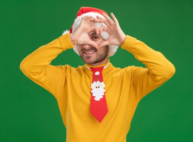 Smiling young caucasian man wearing christmas hat and tie looking at camera doing heart sign in front of eye isolated on green background
