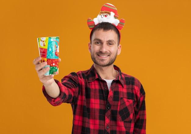 Sorridente giovane uomo caucasico indossando la fascia di babbo natale allungando la tazza di plastica di natale verso la telecamera guardando la telecamera isolata su sfondo arancione con spazio di copia