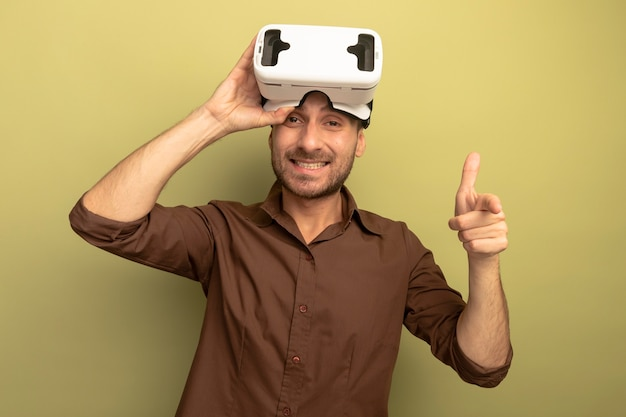 그것을보고 올리브 녹색 배경에 고립 된 카메라를 가리키는 머리에 vr 헤드셋을 입고 웃는 젊은 백인 남자