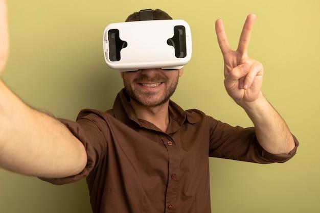 Sorridente giovane uomo caucasico indossando auricolare vr allungando la mano verso la telecamera guardando la telecamera facendo segno di pace isolato su sfondo verde oliva