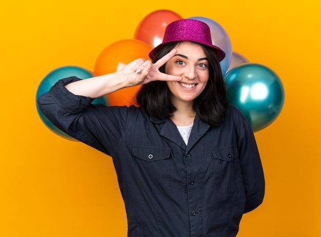 Sorridente giovane ragazza caucasica che indossa un cappello da festa che tiene un mazzo di palloncini dietro la schiena che mostra il simbolo del v-sign vicino all'occhio isolato sul muro arancione