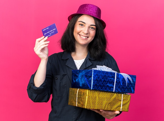 Smiling young caucasian party girl wearing party hat holding gift packages and credit card  isolated on pink wall Free Photo
