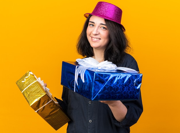 Smiling young caucasian party girl wearing party hat holding gift packages stretching out one towards isolated on orange wall