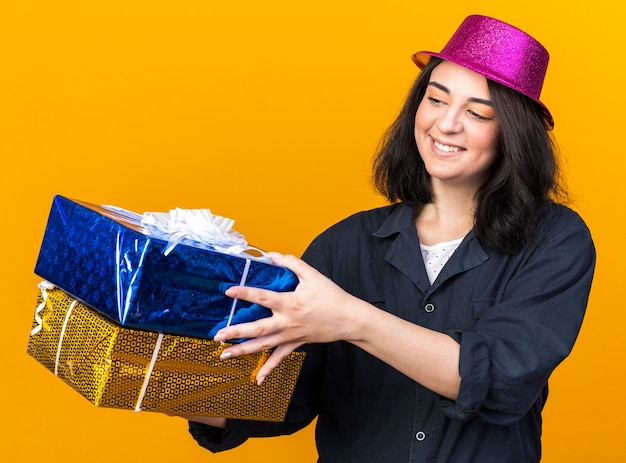 웃고 있는 젊은 백인 파티 소녀가 파티 모자를 쓰고 오렌지색 벽에 격리된 선물 꾸러미를 보고 있다