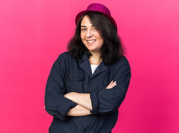 Smiling young caucasian party woman wearing party hat standing with closed posture looking at front isolated on pink wall