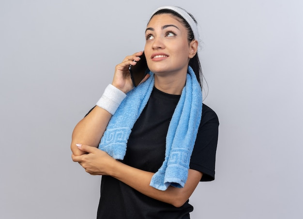 Улыбающаяся молодая кавказская спортивная девушка с повязкой на голову и браслетами разговаривает по телефону с полотенцем на шее, глядя вверх изолированно на белой стене с копией пространства