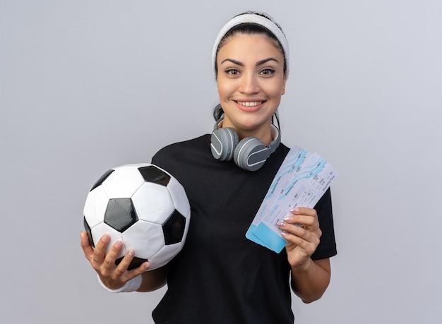 白い壁に隔離された正面を見て飛行機のチケットとサッカーボールを保持している首の周りにヘッドフォンでヘッドバンドとリストバンドを身に着けている若い白人のスポーティな女の子の笑顔