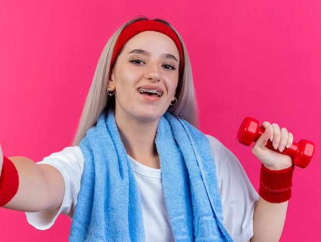 Улыбающаяся молодая кавказская спортивная девушка с подтяжками и с полотенцем на шее с повязкой на голову и браслетами держит гантели, глядя в камеру