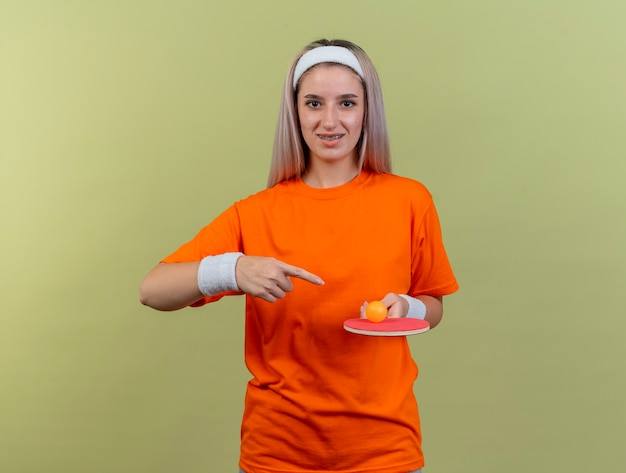 ヘッドバンドとリストバンドを身に着けているブレースを持つ白人のスポーティな若い女の子の笑顔を保持し、ラケットのピンポン ボールを指す