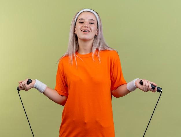 Улыбающаяся молодая кавказская спортивная девушка с подтяжками, носящая повязку на голову и браслеты, держит прыжки со скакалкой
