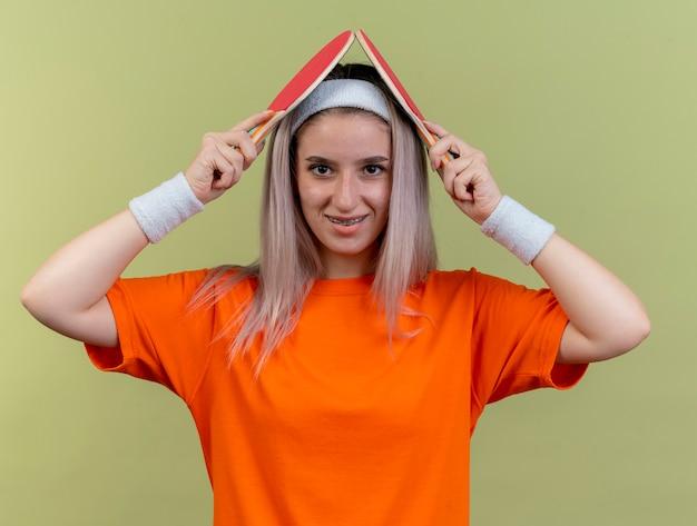 Sorridente giovane ragazza sportiva caucasica con bretelle che indossa fascia e braccialetti tiene le racchette da ping-pong sopra la testa