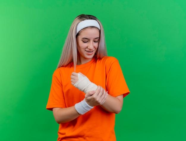 Sorridente giovane ragazza sportiva caucasica con bretelle che indossa fascia e braccialetti mette la mano e guarda il braccio