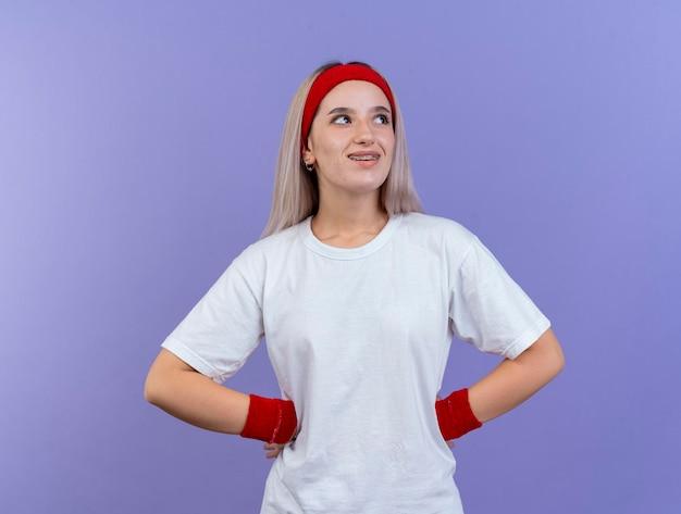 머리띠를 착용 중괄호와 웃는 젊은 백인 스포티 한 소녀