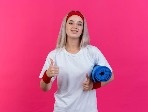 Sorridente giovane ragazza sportiva caucasica con le parentesi graffe che indossa la fascia