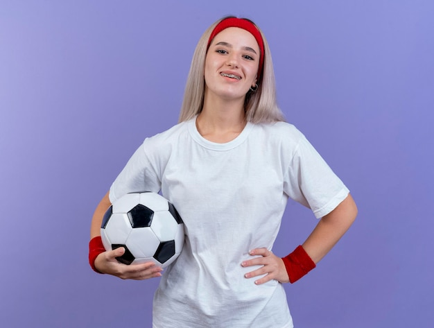 ヘッドバンドを身に着けている中かっこで笑顔の若い白人スポーティな女の子