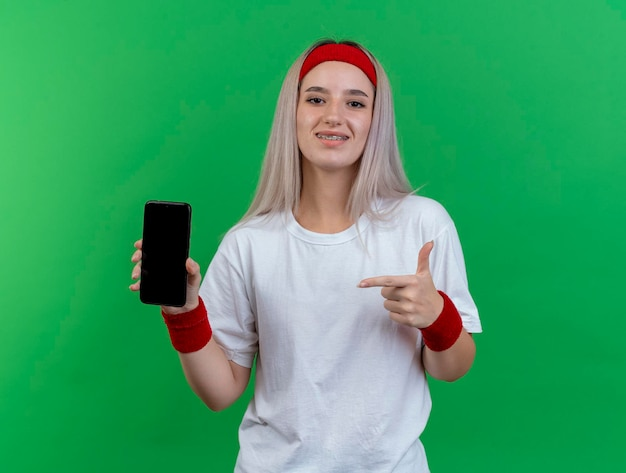 Улыбающаяся молодая кавказская спортивная девушка с подтяжками в головной повязке
