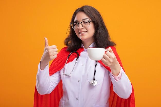 Sorridente giovane ragazza caucasica del supereroe che indossa l'uniforme del medico e lo stetoscopio con gli occhiali che tengono una tazza di tè che mostra il pollice in su isolato sul muro