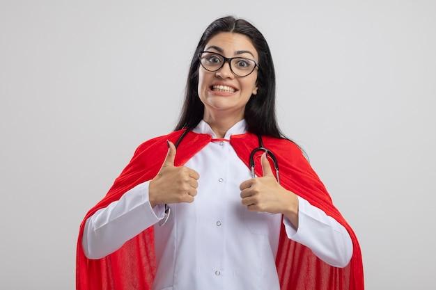 흰색 배경에 고립 엄지 손가락을 보여주는 카메라를보고 안경과 청진기를 입고 젊은 백인 슈퍼 히어로 소녀 미소