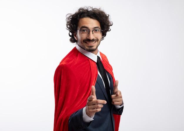 Улыбающийся молодой кавказский супергерой в оптических очках в костюме с красным плащом стоит боком, указывая на камеру двумя руками, изолированными на белом фоне с копией пространства