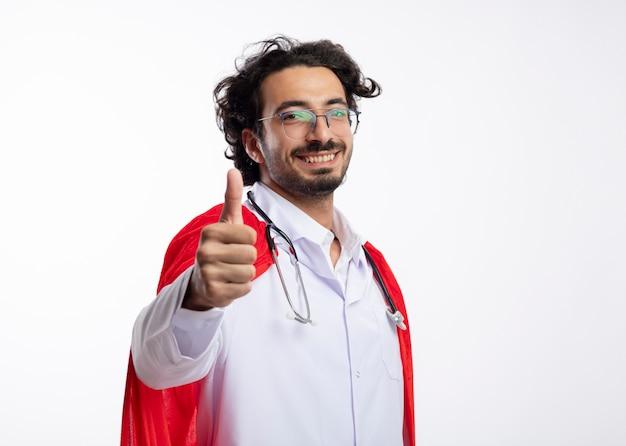 Sorridente giovane supereroe caucasico con occhiali ottici che indossa l'uniforme da medico con mantello rosso e con lo stetoscopio intorno al collo pollice in alto