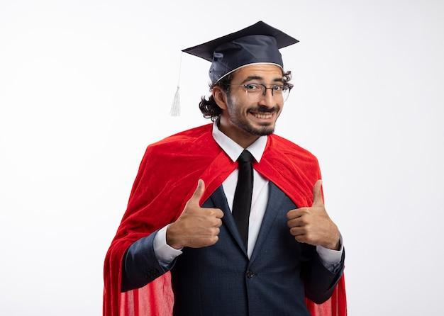 Sorridente giovane indoeuropeo supereroe uomo in vetri ottici che indossa tuta con mantello rosso e cappello di laurea pollice in alto con due mani isolate su priorità bassa bianca con lo spazio della copia