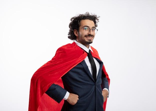 Sorridente giovane uomo caucasico supereroe in occhiali ottici che indossa tuta con mantello rosso si leva in piedi lateralmente mettendo le mani sulla vita isolato su priorità bassa bianca con lo spazio della copia