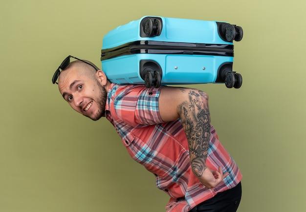 Sorridente giovane viaggiatore caucasico uomo che tiene la valigia sulla schiena isolata su sfondo verde oliva con spazio copia