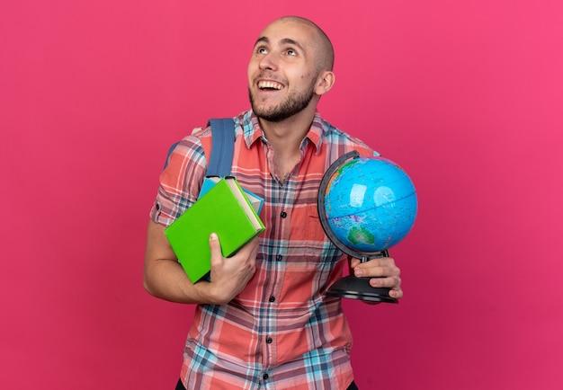 コピースペースでピンクの背景に分離された本と地球を見上げるバックパックと笑顔の若い白人旅行者の男性