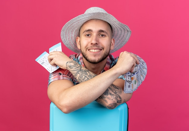 Sorridente giovane viaggiatore caucasico con cappello da spiaggia di paglia in possesso di biglietti aerei e denaro in piedi dietro la valigia isolata su sfondo rosa con spazio di copia