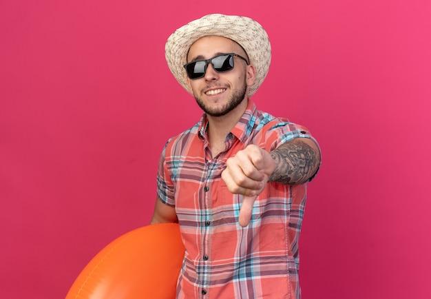 Sorridente giovane viaggiatore caucasico con cappello da spiaggia di paglia in occhiali da sole che tiene anello da bagno e pollice verso il basso isolato su sfondo rosa con spazio di copia