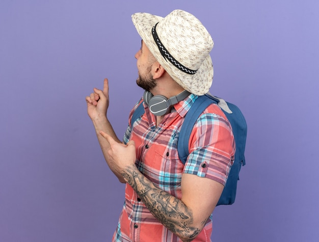 Smiling young caucasian traveler man with straw beach hat and with backpack looking and pointing back isolated on purple background with copy space